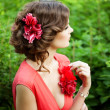 Stock Photo: Beautiful womwith flower in hairstyle