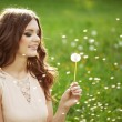 Beautiful woman blowing a dandelion — Stockfoto