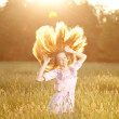 Smiling woman in a field at sunset with flying hair — Stock Photo #31005885