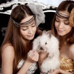 Two beautiful stylish womans with a rabbit — Stock Photo