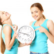 Two smiling women holding a clock — Foto de Stock