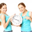 Two smiling women holding a clock — Foto Stock