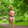 Stock Photo: Womplaying sports, running in park