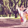 Woman in a bright dress flying in the forest — Stock Photo