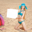 Woman holding white blank poster on the beach — Stock Photo #31006863