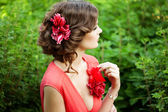 Beautiful woman with a flower in the hairstyle — Stock Photo