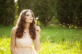 Beautiful woman blowing a dandelion — Stock Photo