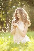 タンポポを吹いている美しい女性 — ストック写真