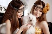 Två vackra snygga tjejer med en kanin — Stockfoto