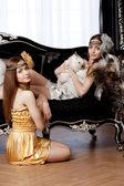 Dos hermosas chicas con estilo con un conejo — Foto de Stock