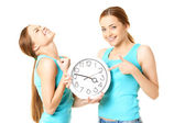 Two smiling women holding a clock — Stock Photo