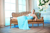 Luxury woman in fashionable dress in rich interior — Stock Photo