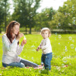 Beauty Mom and baby outdoors. Happy family playing in nature. Mo — Stock Photo #38545191