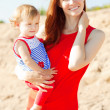 Beautiful Mom and baby outdoors. Happy family playing on the bea — Stock Photo