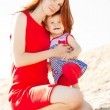 Stock Photo: Beautiful Mom and baby outdoors. Happy family playing on bea