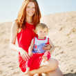 Beauty Mom and baby outdoors. Happy family playing on the beach. — Stock Photo #38545399