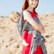 Beautiful woman with a baby in a sling. Mom and baby. Mother and — Stock Photo