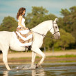 Stock Photo: Young womon horse. Horseback rider, womriding horse on b
