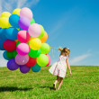 Little girl holding colorful balloons. Child playing on green — Stock fotografie #38545895