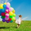 Stock Photo: Little girl holding colorful balloons. Child playing on green