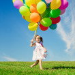 Stock Photo: Little girl holding colorful balloons. Child playing on a green