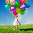 Little girl holding colorful balloons. Child playing on a green — Stock Photo #38545907