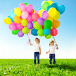 Little girl holding colorful balloons. Child playing on a green — Stock Photo #38545937