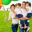Stock Photo: Happy family holding colorful balloons. Mom, ded and two daughte
