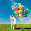 Happy family holding colorful balloons. Mom, ded and two daughte — Stock Photo #38545947