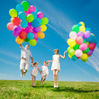 Happy family holding colorful balloons outdoor. Mom, ded and two — Stock Photo #38545951