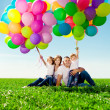 Happy family holding colorful balloons. Mom, ded and two daughte — Stock Photo #38545963