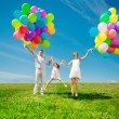 Happy family holding colorful balloons. Mom, ded and two daughte — Stock Photo #38545975