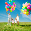 Happy family holding colorful balloons outdoor. Mom, ded and two — Stock Photo #38545977