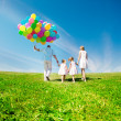 Stock Photo: Happy family holding colorful balloons outdoor. Mom, ded and two