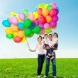 Happy family holding colorful balloons. Mom, ded and two daughte — Stock Photo #38545981