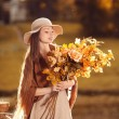 Young woman walking in autumn park with a bouquet of fall leav — Zdjęcie stockowe