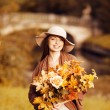 Young woman walking in autumn park with a bouquet of fall leav — Stockfoto