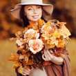 Stock Photo: Young fashion woman walking in autumn park with a bouquet of fa