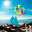Luxury fashion woman with balloons in hand on the beach against — Stock Photo #38546155