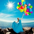 Luxury fashion woman with balloons in hand on the beach against — Stock Photo #38546171