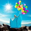 Luxury fashion woman with balloons in hand on the beach against — Stock Photo #38546177
