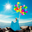 Luxury fashion woman with balloons in hand on the beach against — Stock Photo #38546215