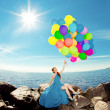 Stock Photo: Luxury fashion womwith balloons in hand on beach against