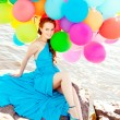 Luxury fashion woman with balloons in hand on the beach against — Stock Photo #38546261