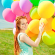 Luxury fashion woman with balloons in hand on the field against — Stock Photo #38546335