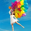 Beautiful young stylish woman with multi-colored rainbow balloon — Stock Photo #38546383