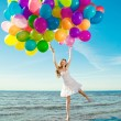 Beautiful young stylish woman with multi-colored rainbow balloon — Stock Photo #38546387
