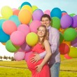 Young healthy beauty pregnant woman with her husband and balloon — Stock Photo #38546817
