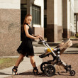 Stock Photo: Trendy modern mother on city street with pram. Young mother