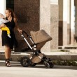 Fashionable modern mother on a city street with a pram. Young mo — Stock Photo